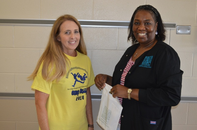 Lori Watkins, Certified Medical Assistant at Low Country Dermatology, delivers goody bags filled with sunscreen, lip balm, shampoo, conditioner, soap and hand sanitizer to Camp Buddy Director, Pam Hussey for all campers