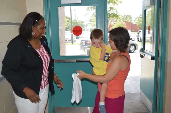 Lori Watkins, Certified Medical Assistant at Low Country Dermatology, hands a goody bag to camper, Hudson Miles, and his mother, Kamarie Miles